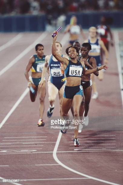 American athlete LaTasha Colander raises her baton in celebration as she crosses the finish line in first place for the United States team to win the...