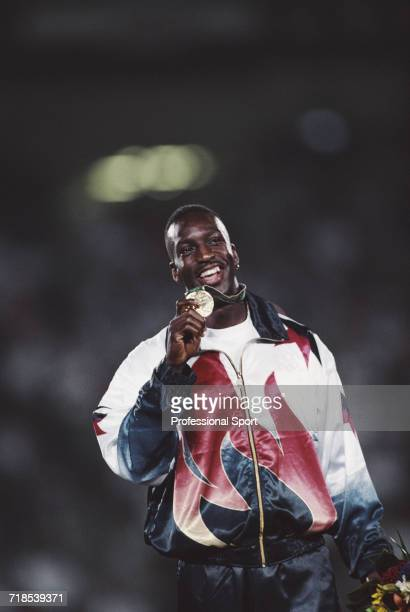 American athlete Michael Johnson holds up his gold medal on the medal podium after finishing in first place with a world record time in the Men's 200...