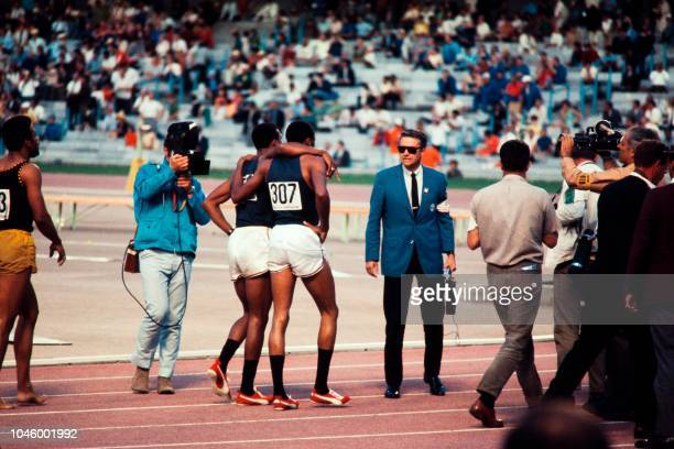 American athlete Tommie Smith and compatriot John Carlos, wearing black socks, congratulate each other after the men's 200m final during the Mexico...