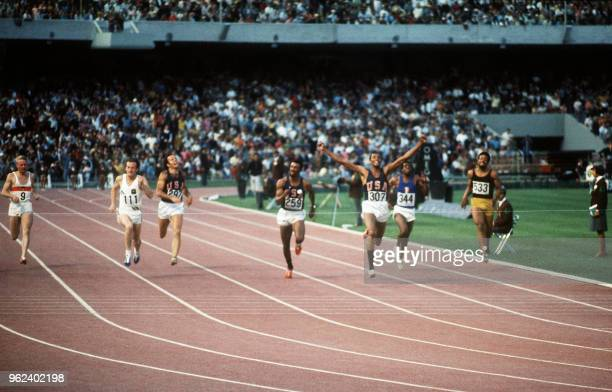 American athlete Tommie Smith wearing black socks jubilates after crossing the finish line of the men's 200m final ahead of Australian Peter Norman...