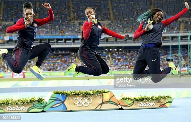 American athletes who won the gold silver and bronze medals in the women's 100meter hurdles at the Rio de Janeiro Olympics leap near the podium on...