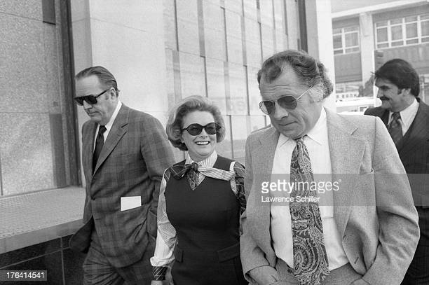 American attorney F Lee Bailey walks with University of California regent Catherine Hearst and her husband chairman of the Hearst Corporation board...
