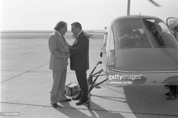 American attorneys F Lee Bailey and J Albert Johnson talk as they stand on the tarmac beside a helicopter at an unidentified airfield San Francisco...