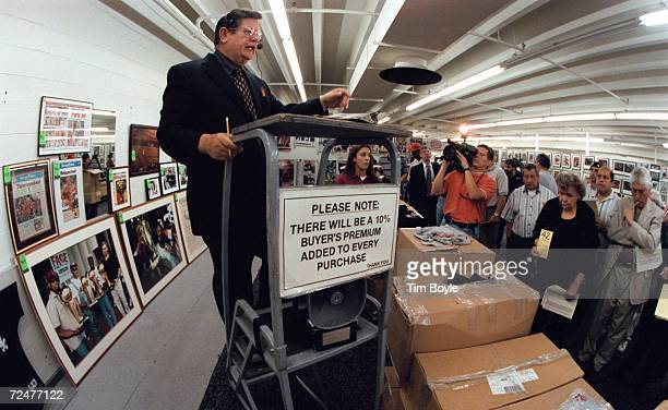 American Auction Associates auctioneer Donald Dodge center barks out prices for boxes of Michael Jordan's Restaurant tshirts June 6 to be auctioned...