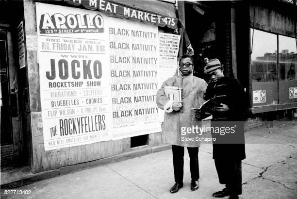 American author and activist James Baldwin stands with his nephew on a sidewalk in Harlem New York New York 1963 Posters behind them advertise as...