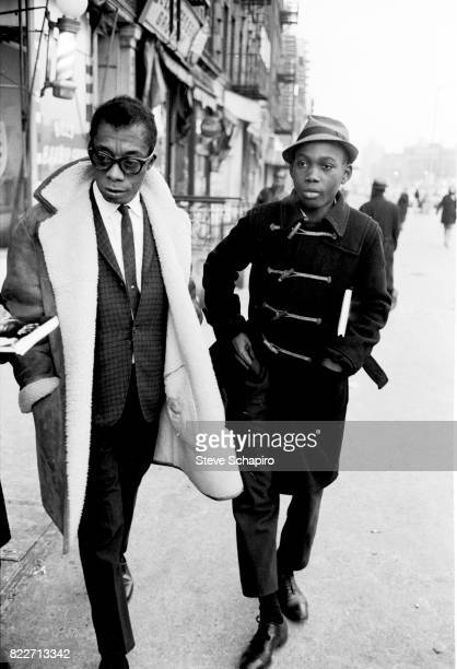 American author and activist James Baldwin walks with his nephew along a sidewalk in Harlem New York New York 1963