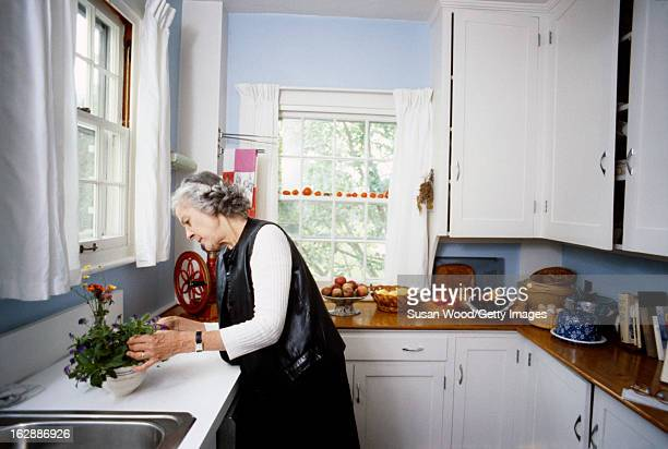 American author and critic Mary McCarthy works with some flowers in the kitchen of her summer home, Castine, Maine, 1980.
