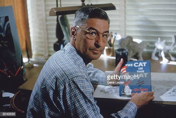 American author and illustrator Dr Seuss sits at his drafting table in his home office with a copy of his book, 'The Cat in the Hat', La Jolla,...