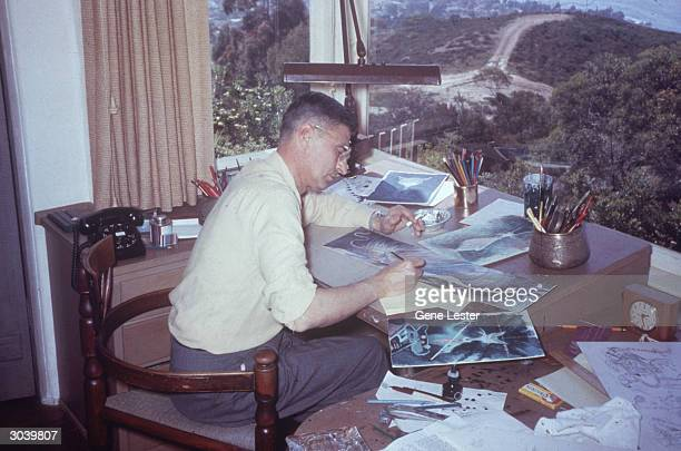 American author and illustrator Dr. Seuss , works on illustrations for one of his children's books at his desk at home in La Jolla, California, April...