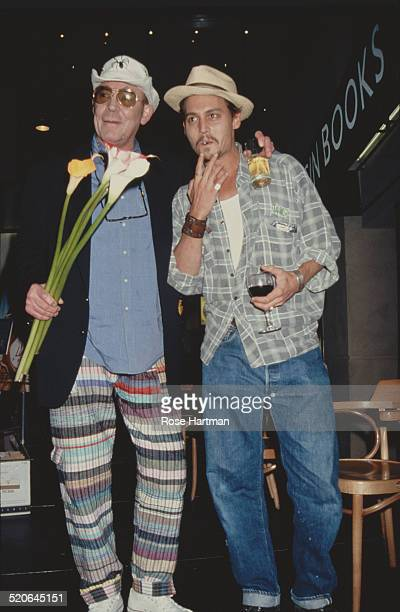 American author and journalist Hunter S Thompson and actor Johnny Depp pose together on a podium in the atrium of the Times Square Virgin Megastore...