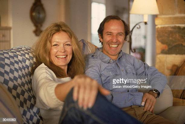 American author and political activist Gloria Steinem and Canadianborn businessman Mortimer Zuckerman sit on a couch and laugh 1984