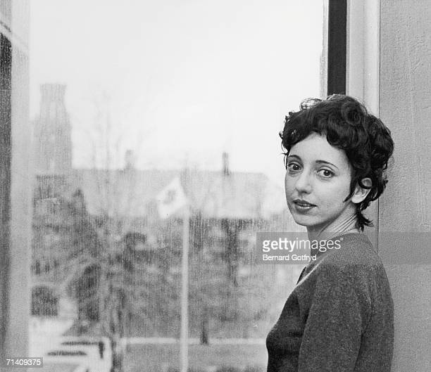 American author and professor Joyce Carol Oates looks over her shoulder as she stands by a window overlooking Dillon Hall on a rainy day University...