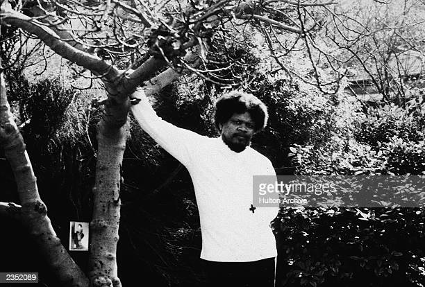 American author and satirist Ishmael Reed posing next to tree 1975