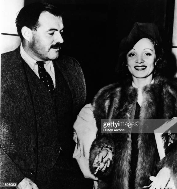 American author Ernest Hemingway and German-born actor Marlene Dietrich stand together while attending an event, 1930s. Dietrich holds a copy of one...
