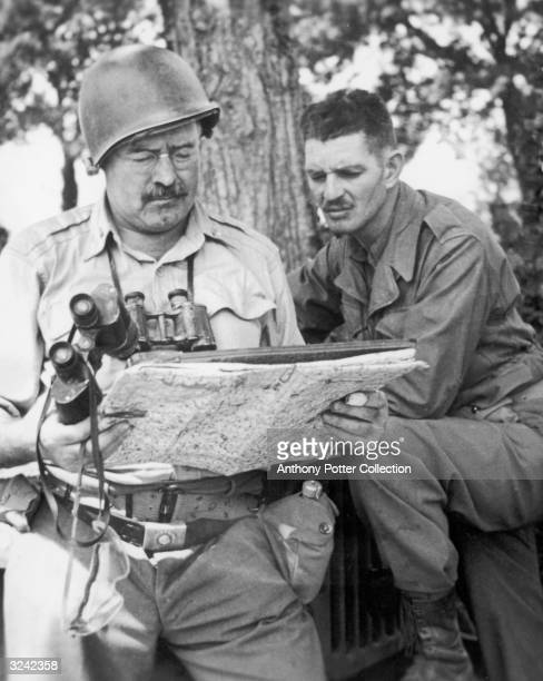 American author Ernest Hemingway confers with an officer while traveling with United States troops in Europe as a World War II correspondent.