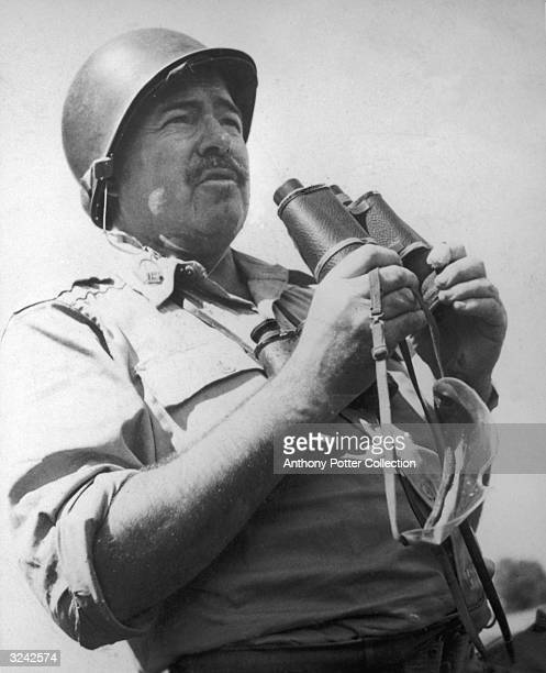 American author Ernest Hemingway holds a pair of binoculars and wears a helmet while traveling with United States troops in Europe as a World War II...