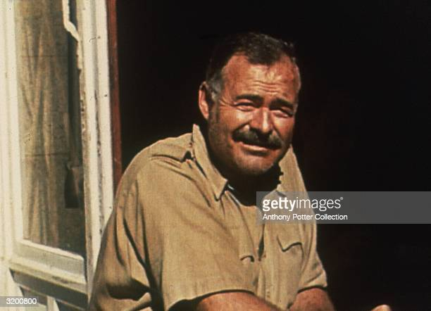 American author Ernest Hemingway squinting as he sits near an open window in the sun Mont St Michel France Hemingway was in France covering World War...