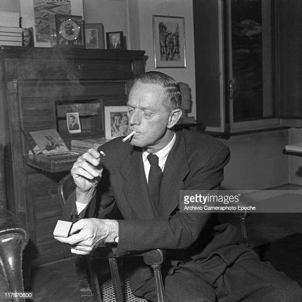 American author Erskine Caldwell wearing a suit and a tie sitting on a chair and lighting a cigarette with a match in his studio in Milan 1953