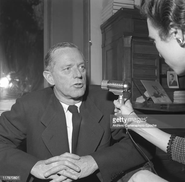 American author Erskine Caldwell wearing a suit and a tie sitting on a chair in his studio in Milan granting an interview to a journalist holding a...