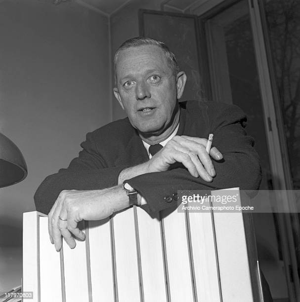 American author Erskine Caldwell wearing a suit and a tie smoking a cigarette portrayed while leaning on some books in his studio in Milan 1953