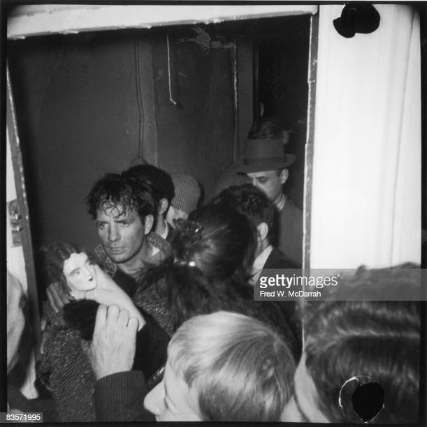 American author Jack Kerouac holds a doll as he leaves the Artist's Club after a New Year's Eve party New York New York January 1 1959 Mostly...