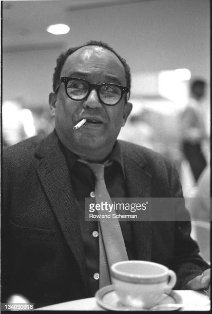 American author Langston Hughes sits at a table and smokes a cigarette on the set of the television special 'The Strollin' 20's' , for whcih he wrote...