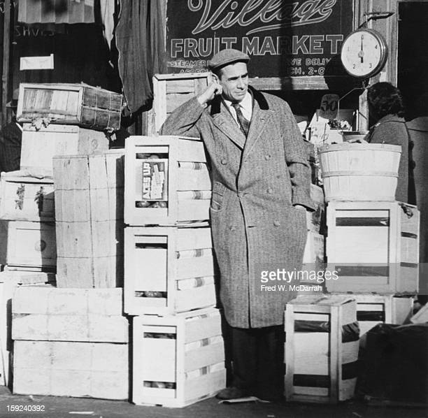 American author Robert Nichols leans on a crate outside the Village Fuit Market New York New York November 30 1959