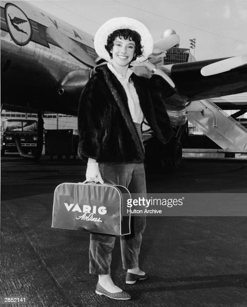 American author Rona Jaffe stands on the tarmac in front of a Varig Airlines plane at Idlewild Airport following the completion of filming 1959's...