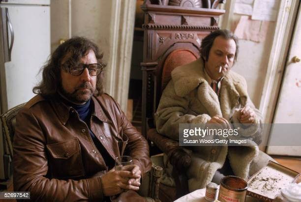 American author screenwriter and satirist Terry Southern left holds a drink as actor Rip Torn lights up a rolled cigarette in his Chelsea apartment...