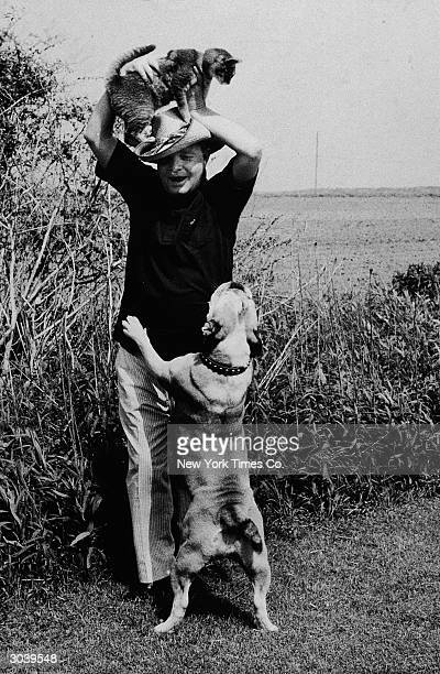 American author Truman Capote smiles while playing with his pet cat and dog in Sagaponack Long Island New York City June 5 1971