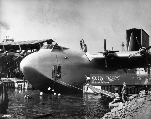 American aviator and industrialist Howard Hughes atop his flying boat and the world's largest airplane 'The Spruce Goose' directing operations for...