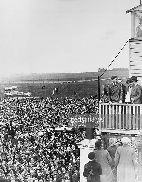 American aviator Charles Lindbergh stands on the balcony of a control tower to address a crowd of around a hundred thousand on his arrival at Croydon...