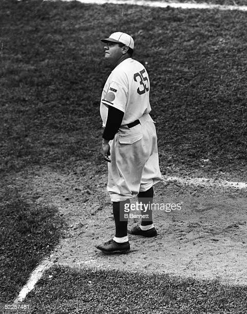 American baseball legend Babe Ruth watches a high fly ball from the coach's box at Ebbets Field during his first game as coach for the Brooklyn...