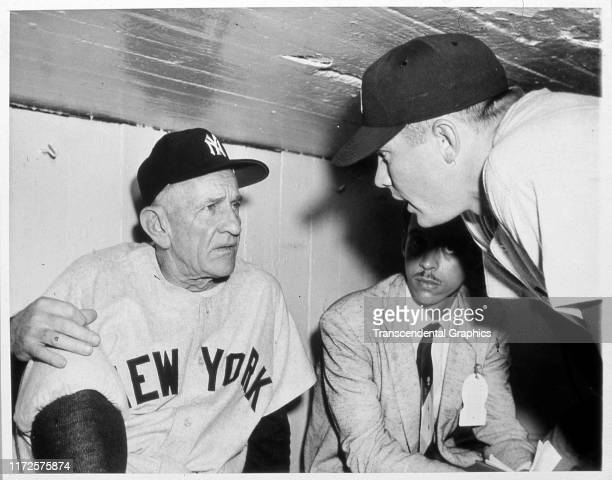 American baseball manager Casey Stengel of the New York Yankees talks to player Mickey Mantle in the dugout before game three of World Series against...