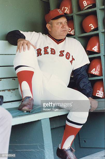 American baseball manager Don Zimmer of the Boston Red Sox sits on a bench in the dugout and watches the on-field action in Fenway Park, Boston,...