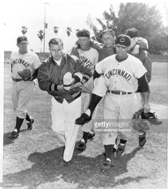 American baseball pitcher Ken Raffensberger of the Cincinnati Reds is carried off the field by his teammates after an injury during spring training...