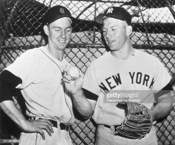 American baseball player Al Kaline of the Detroit Tigers looks at a baseball held by Mickey Mantle of the New York Yankees Detroit Michigan 1956