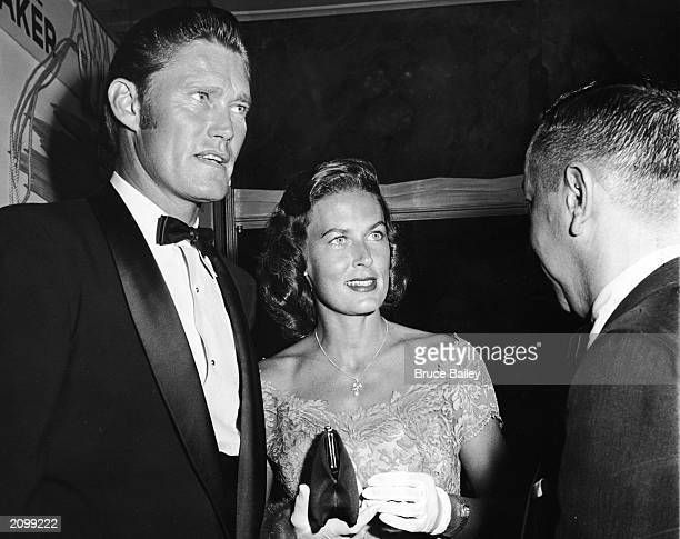 American baseball player and actor Chuck Connors and his wife Elizabeth Jane Riddell attend the premiere of the film 'The Big Country' directed by...