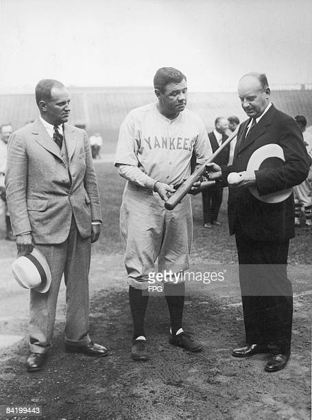 American baseball player Babe Ruth of the New York Yankees poses with two unidentified men late 1920s