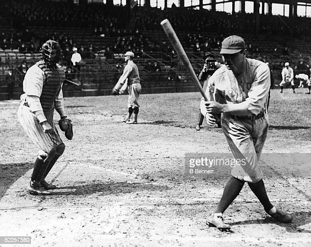 American baseball player Babe Ruth of the New York Yankees takes a swing during pregame warm ups or a team practice as another photographer takes his...