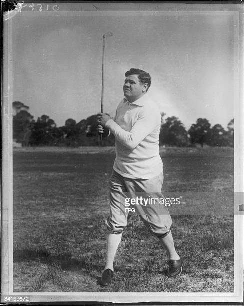 American baseball player Babe Ruth plays golf on an unidentified course early 1920s
