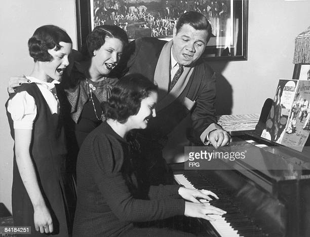 American baseball player Babe Ruth sings with his family as they celebrate his 40th birthday New York New York February 7 1940 At the piano is...