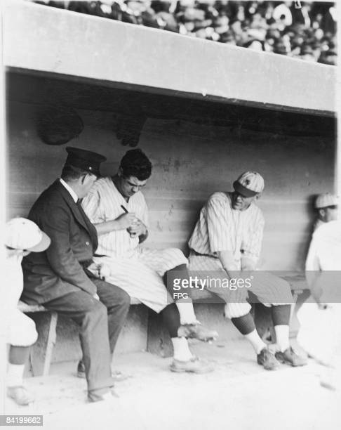 American baseball player Babe Ruth sits in the dugout and watched by a teammate signs a baseball for an unidentified man in a cap 1921