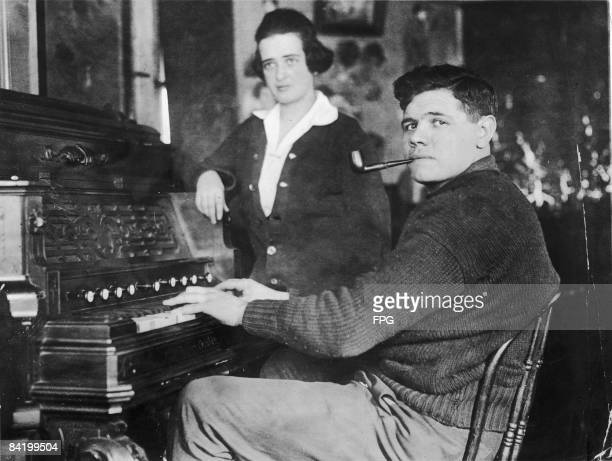 American baseball player Babe Ruth smokes a pipe as he plays a piano while his wife Helen Ruth stands next to him 1910s