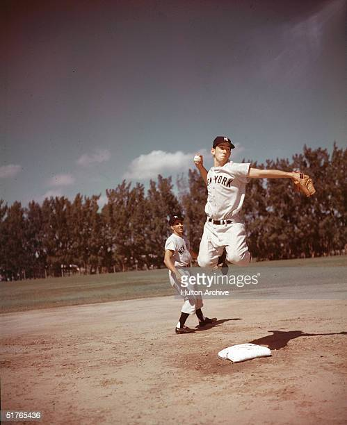 American baseball player Billy Martin jumps into the air as he throws the ball while teammate Phil Rizutto watches mid 1950s Both players are dressed...