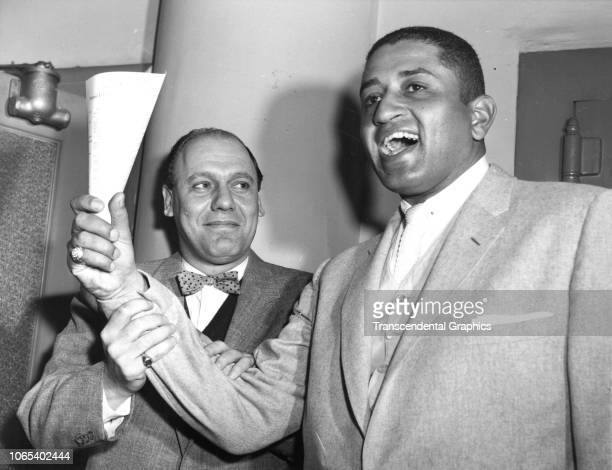 American baseball player Don Newcombe celebrates with his agent following the signing of his new contract Brooklyn New York New York winter 1957