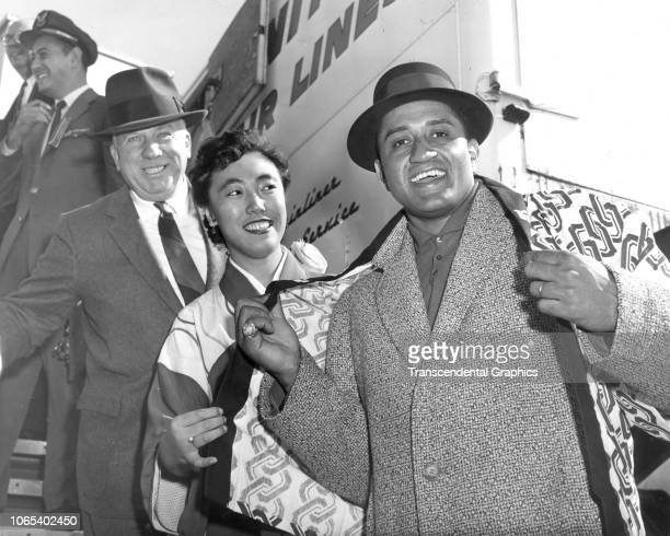 American baseball player Don Newcombe smiles as an unidentified woman drapes him in a kimono while baseball commissioner Warren Giles stands behind...
