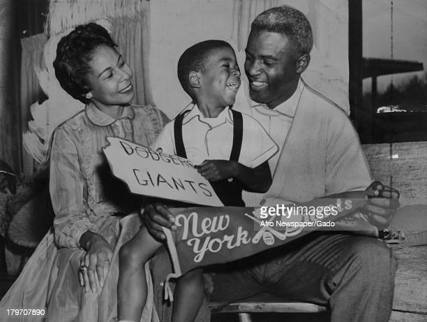 American baseball player Jackie Robinson formerly of the Brooklyn Dodgers and his fouryearold son David laugh it up in the trophy room of their...