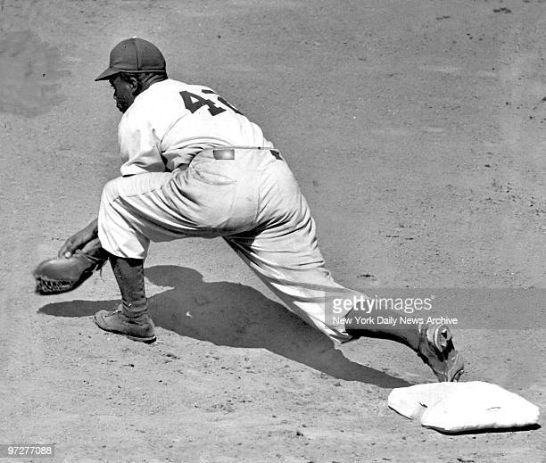 Jackie Robinson of the Brooklyn Dodgers keeps a foot on first base as he takes a throw during a game against the New York Giants