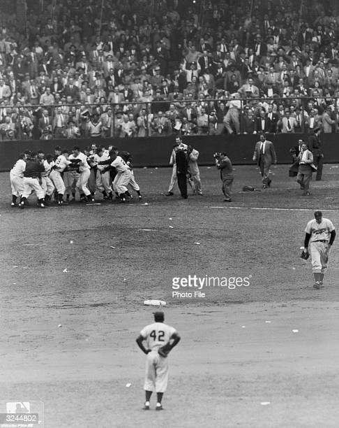 American baseball player Jackie Robinson , of the Brooklyn Dodgers, watches as members of the New York Giants mob their teammate Bobby Thomson at...